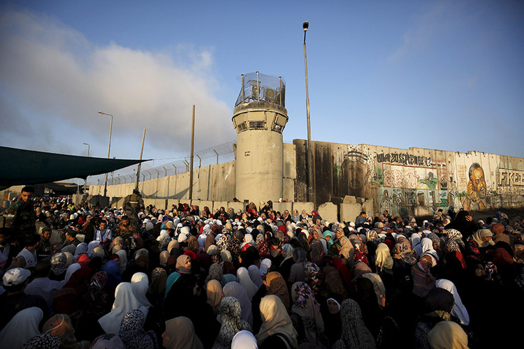 Palestinians wait to show their identity cards to Israeli security officers as they make their way to attend the third Friday prayer of Ramadan in Jerusalem's al-Aqsa mosque, at Qalandia checkpoint near the West Bank city of Ramallah