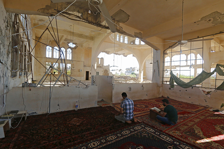 Men pray inside a damaged mosque during the holy month of Ramadan in Qmenas village, in Idlib province