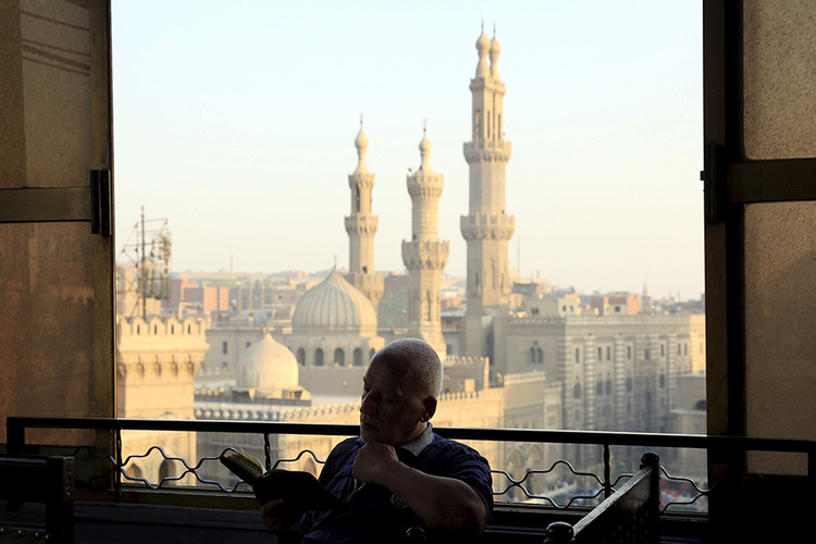 Man reads the Koran minutes before sunset as he waits to break his fast and have his Iftar meal near Al-Azhar mosque, in the old Islamic area of Cairo, Egypt