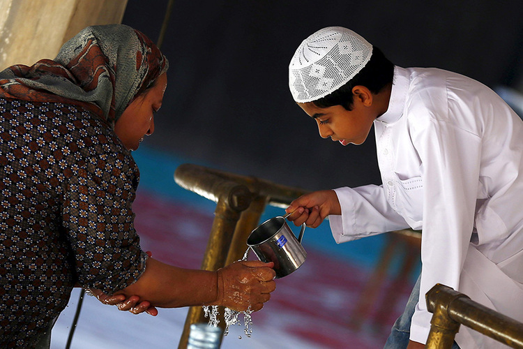 """An Egyptian boy helps his grandmother to wash her hands, as she performs ablution, before  the """"Al Zohar"""" afternoon prayers during the holy month of Ramadan inside Al Sultan Hassan mosque in the old Islamic area of Cairo"""